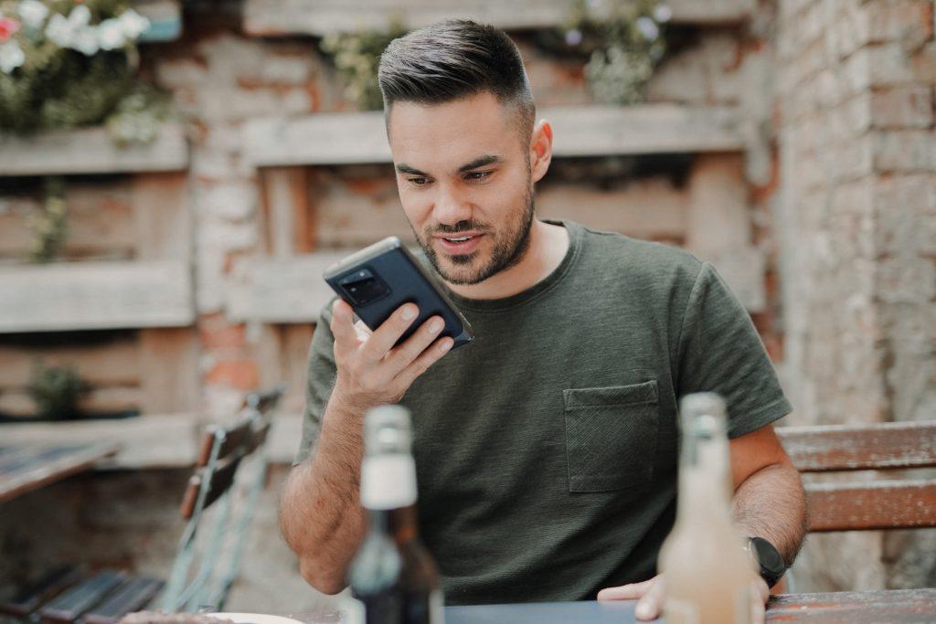 Homem cis branco de camisa preta utilizando um celular para fazer uma pesquisa por voz
